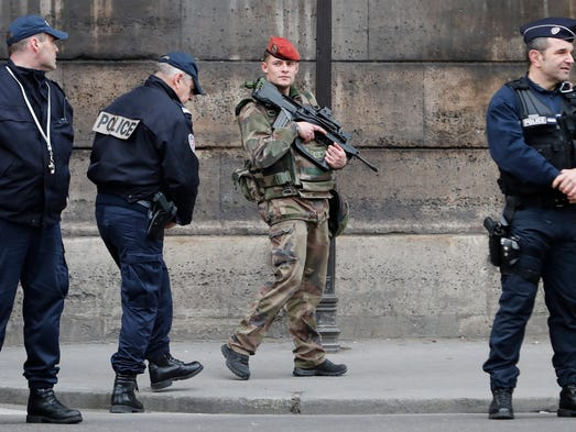 Policemen stand guard near the Louvre museum in Paris,