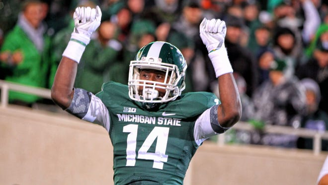 Oct 4, 2014; East Lansing, MI, USA; Michigan State Spartans wide receiver Tony Lippett (14) celebrates a touchdown pass from Michigan State Spartans quarterback Connor Cook (18)(not pictured) during the 1st quarter of a game at Spartan Stadium. Mandatory Credit: Mike Carter-USA TODAY Sports
