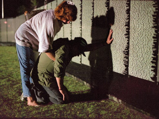 Ken Branden of Indio, a Vietnam veteran from 1966-68, mourns the memory of a friend and comrade while his friend, Debbie Barker of La Quinta, hugs him at the Vietnam Veterans Moving Wall in Palm Desert Civic Center Park at 1 a.m. on Sept. 25, 1997, moments after the wall was opened to the public.