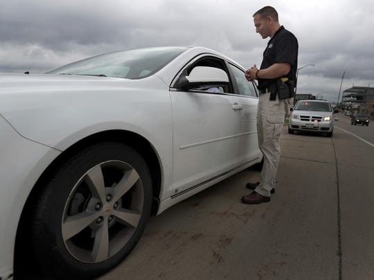 Neenah Police Department investigator Jeremey Bauman talks with a driver during the Crosswalk Violation Enforcement Initiative on Thursday, Sept. 8, 2016 in Neenah, Wis. The initiative is meant to build awareness of pedestrian safety by stopping drivers who fail to yield to pedestrians in crosswalks. Drivers were given a courtesy warning.