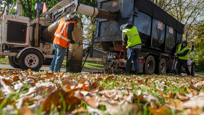Marcotte crews pick up leaves Monday, Oct. 31, 2016, on Woodstock Drive in Port Huron.