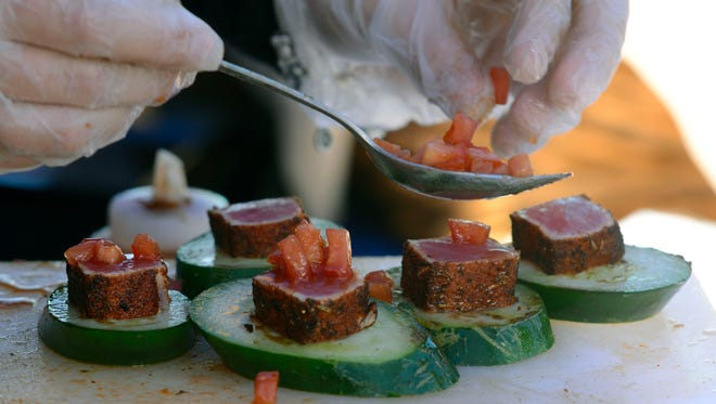 Grilled cucumbers and blackened Ahi tuna is prepared. Patrons got to sample food and wine from six renowned chefs and more than 30 wine selections Sunday during the Pensacola Beach Art and Wine Festival at the Pensacola Beach Boardwalk.