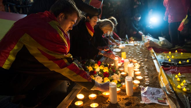 People attend a vigil for the victims of the Brussels attacks in Trafalgar Square in London on March 24, 2016.