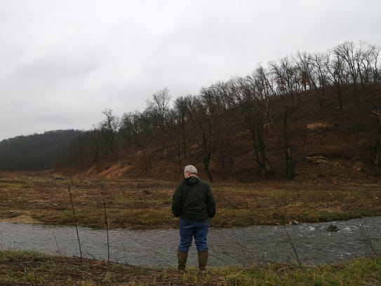 Michael Osterholm, stands on the edge of Waterloo Creek,