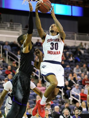 Southern Indiana guard Cortez Macklin (30) shoots past Kentucky Wesleyan forward Sam Williams (3) during the Small College Basketball Hall of Fame Classic at the Ford Center in Evansville, Saturday, Nov. 19, 2016. Southern Indiana beat Kentucky Wesleyan 85-81.
