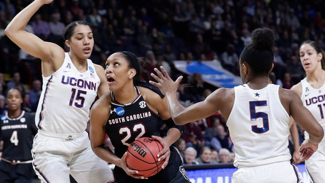 South Carolina's A'ja Wilson (22) drives past Connecticut's Gabby Williams (15) and Crystal Dangerfield (5) during the first half of a regional final at the a women's NCAA college basketball tournament Monday in Albany, N.Y.