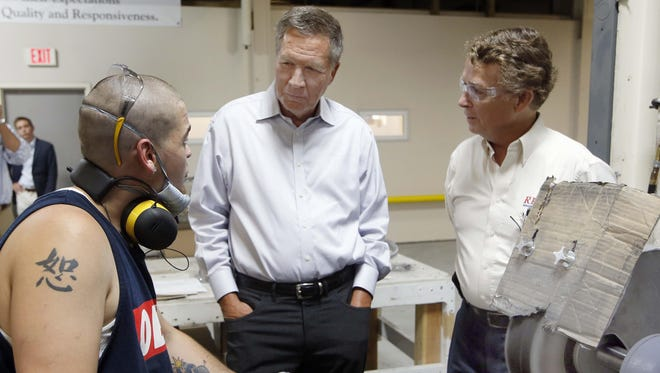 Ohio Gov. John Kasich talks with Harley Staples, left, during a visit Monday at RP Abrasives in Rochester, N.H. Kasich later asked several RP Abrasives to share their biggest dreams.