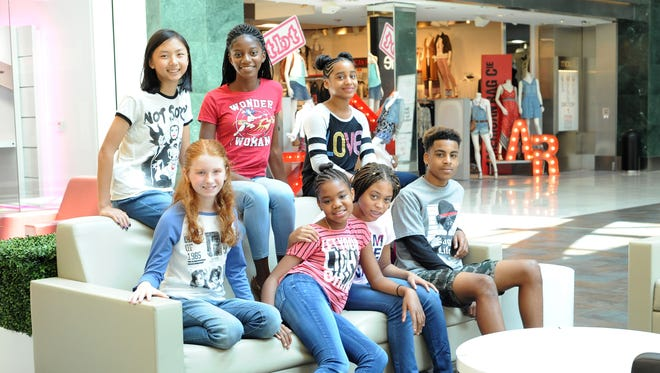 """One of the ways to make a statement is with a T-shirt. This isn't a difficult fashion hack to master. It's just a T-shirt and jeans, right? But it's all about the message if you want your T-shirt game to truly be on point!  (From left, bottom row sitting on couch): Megan Barnard wears a Breakfast Club 1985 Yearbook T-shirt ($24); Whitley Ragland wears a """"Let Your Life Shine"""" T-shirt ($28); Amariah Harrison wears an """"I am the original"""" T-shirt by Tommy Hilfiger ($29.50); Eli Ragland wears a """"Pug life"""" T-shirt by Jem Boys ($18). (From left, top row): Megan Liu wears a """"Not Sorry"""" T-shirt by Mighty Fine Disney Villains ($24); McKenna Samson wears a """"Wonder Woman"""" T-shirt by Bioworld ($24); Naomi Ragland wears a """"Love"""" T-shirt by Rebellious One ($24)."""