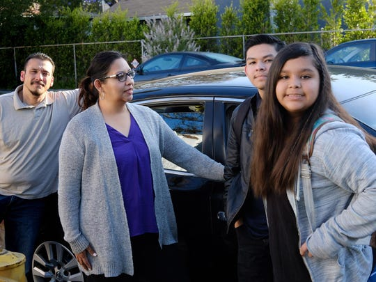 """This Thursday, May 26, 2016 photo shows Enrique Duarte, left, with his wife Lisette and their two children Enrique and Elise before taking them to school in Los Angeles. Duarte is debating where to enroll her 11-year-old daughter. Her 16-year-old son already attends a charter school with many benefits she doesn't see at their neighborhood school, a small learning environment, extra-curricular activities and close attention from teachers. Her daughter, by contrast, is struggling in a low-performing school with a large English learner population, she said. """"It makes me really sad when I hear about parents who are still struggling,"""" she said. (AP Photo/Richard Vogel)"""