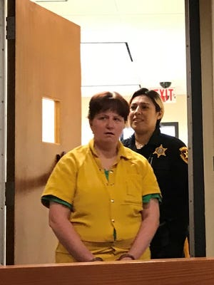 Lynn Bergacs enters Middlesex County Assignment Judge Alberto Rivas courtroom escorted by a sheriff's officer.