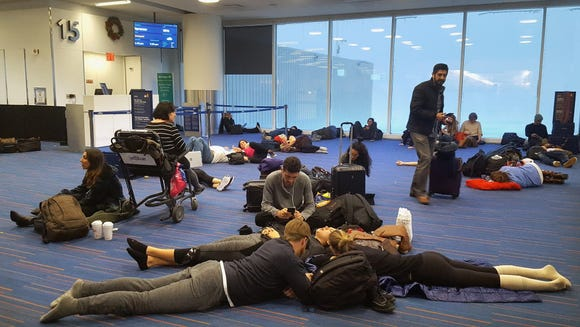 Passengers wait for their delayed flights at gate 15