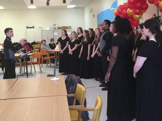 Student director Sam Mossop leads the Hammonton High School Select Choir in song at the Hammonton Senior Nutrition Center on Monday.