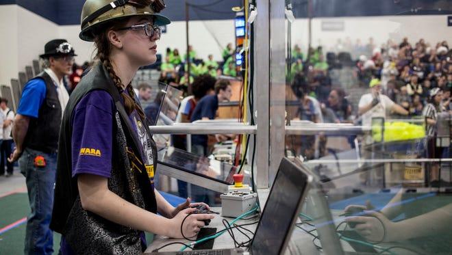 Mecanum Knights member Olivia Hudson, 14, controls a  robot during a 2017 FIRST Robotics District event at Marysville High School.