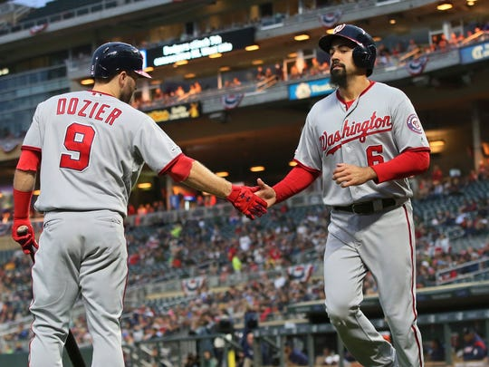 Washington Nationals' Brian Dozier, left, congratulates Anthony Rendon after Rendon scored on a single by Ryan Zimmerman off Minnesota Twins pitcher Martin Perez during the first inning of a baseball game Wednesday, Sept. 11, 2019, in Minneapolis. (AP Photo/Jim Mone)