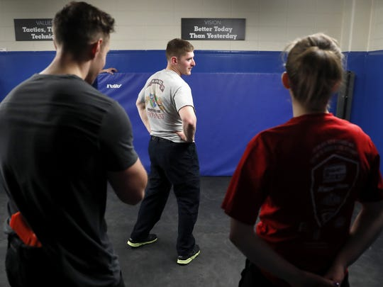 Appleton police officer Michael Chevremont, center, begins to turn around and assess the situation after officers Nic Meyer and Joanna Kolosso hid a firearm in Meyer's waistband during Advanced Defense and Arrest Tactics training April 11. Chevremont needed to determine who had the weapon based on body language and attempt to disarm them as they drew the weapon.