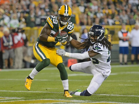 Green Bay Packers receiver James Jones (89) scores a first quarter touchdown against Seattle Seahawks cornerback Richard Sherman (25) at Lambeau FIeld.