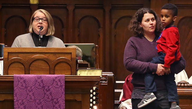 "The Rev. Melody Merida (left) of LifeJourney Church in Indianapolis spoke Wednesday, March 4, 2015, at a Freedom Indiana faith vigil at Roberts Park United Methodist Church. She was accompanied by her wife, Kristin Herrmann (holding their son, Brody Herrmann). The vigil was organized to protest a ""religious freedom"" proposal now before the Indiana House."