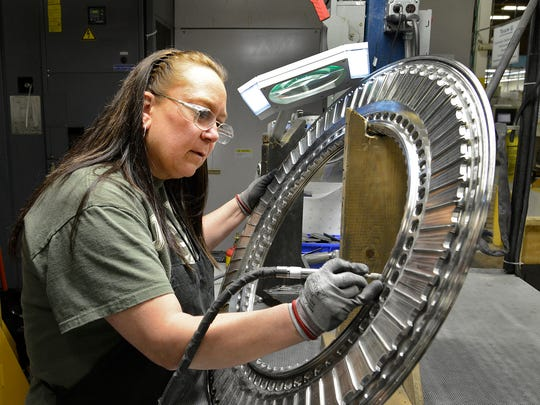 Rhonda Harris uses a small tool to de-burr a jet engine part at the Asheville GE Aviation plant.