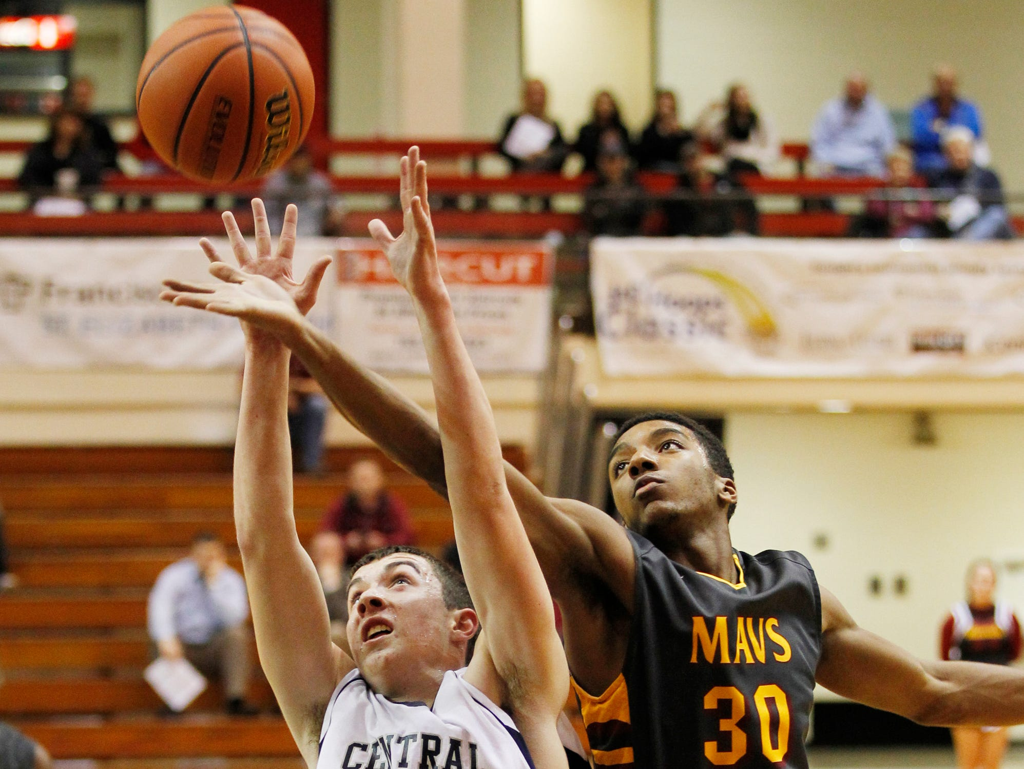 McCutcheon's Charles Phinisee reaches over Trent Thompson of Central Catholic in an attempt grab a rebound in the J&C Hoops Classic Tuesday, December 1, 2015, at Lafayette Jeff. McCutcheon won in a landslide 114-44 over Central Catholic.