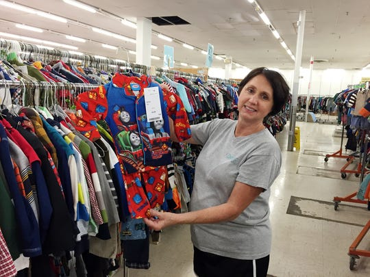 Volunteer worker Levis Henshaw shows off some of the children's wear at a previous Encores sale. Henshaw was first introduced to Encores eight years ago while shopping for her grandchildren.
