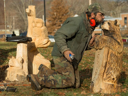 Kevin Black of Tyrone blows on the nose of one his chainsaw sculpture pieces to get the paint to dry Saturday afternoon at Winterfest 2016 in Spencer.
