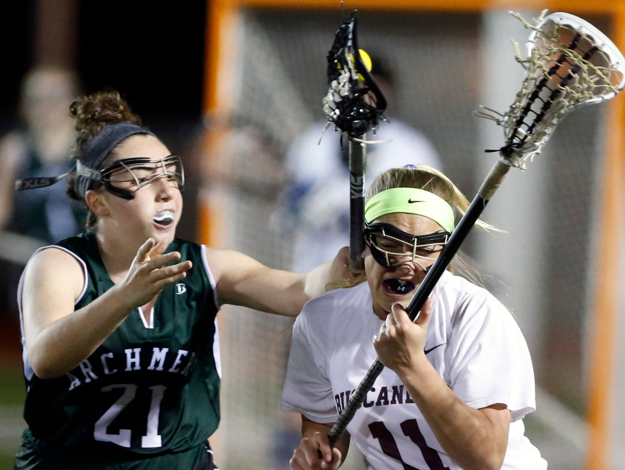 Archmere's Olivia Baldi gets the ball but also contacts Caravel's Lauren Phillips on a stick check in the second half of Caravel's home win, 11-9.