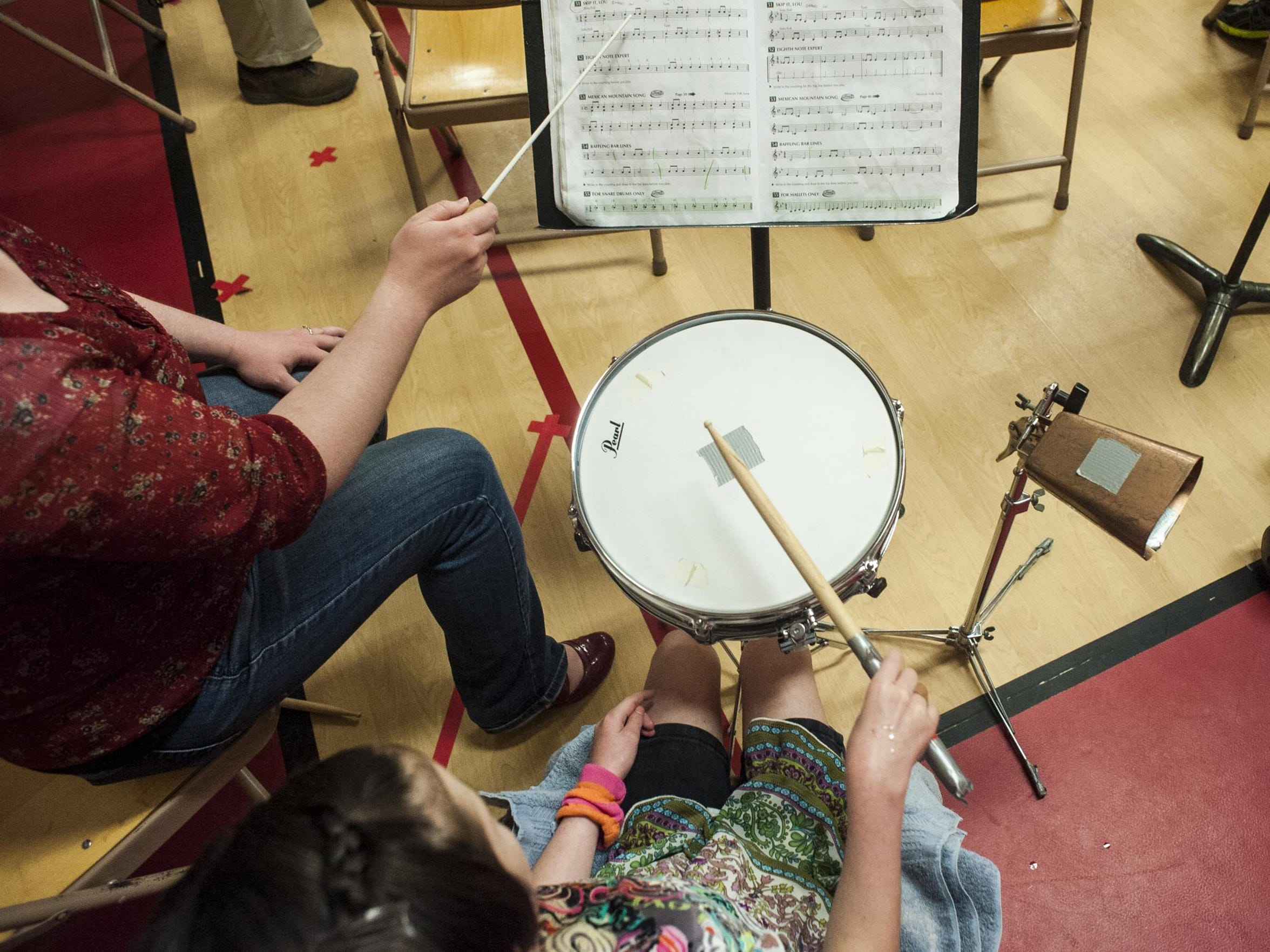 Katie plays snare drum and cowbell while her aide,