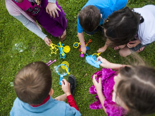 Children play with bubbles during a home-school kickoff