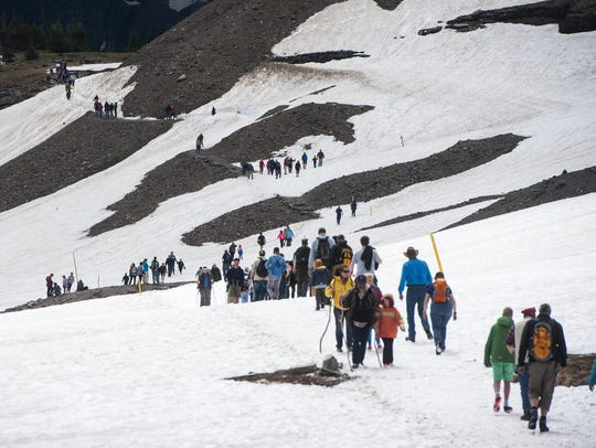 Dozens of hikers traverse a snowy path to the Hidden