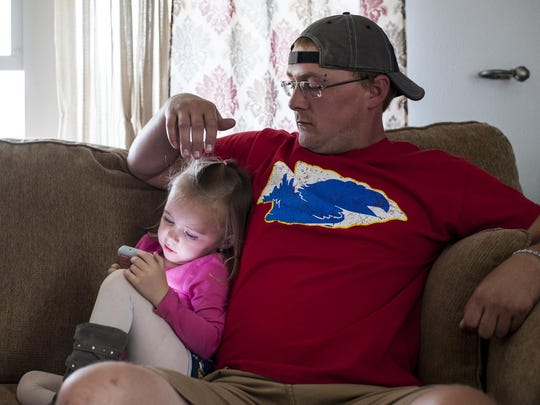 Jason Triplett sits with his 3-year-old daughter Marlie on the couch in their Habitat for Humanity home Wednesday.