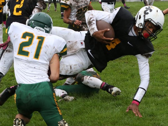 St. Catherine's quarterback Da'Shaun Brown lunges for extra yards before Martin Luther's Mikey Rohleder brings him down.