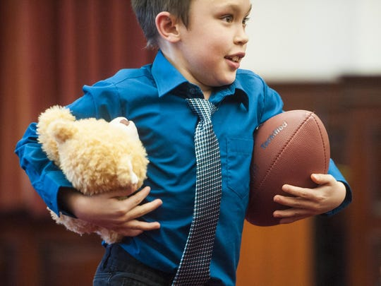 Dante James Farmer, 7, leaves with a football and teddy bear under each arm during the adoption ceremony in the Cascade County Courthouse on Thursday afternoon.