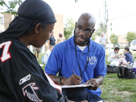 Kevin Gaines, an outreach workers with RVRC, speaks with Tanya Davis outside the Sunday Breakfast Mission in Wilmington as he makes contact with homeless people to offer social services around northern Delaware in Sept. 2014.