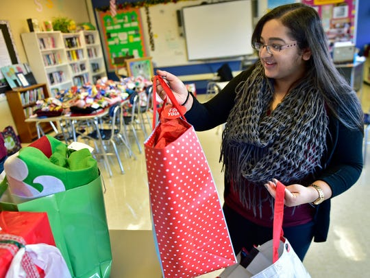 Riya Patel collects bags filled with gifts at CASHS on MOnday, December 19, 2016. CASHS students are stuffing stockings for the holidays that will be given to people at the Children's Aid Society and other places that fill the need.