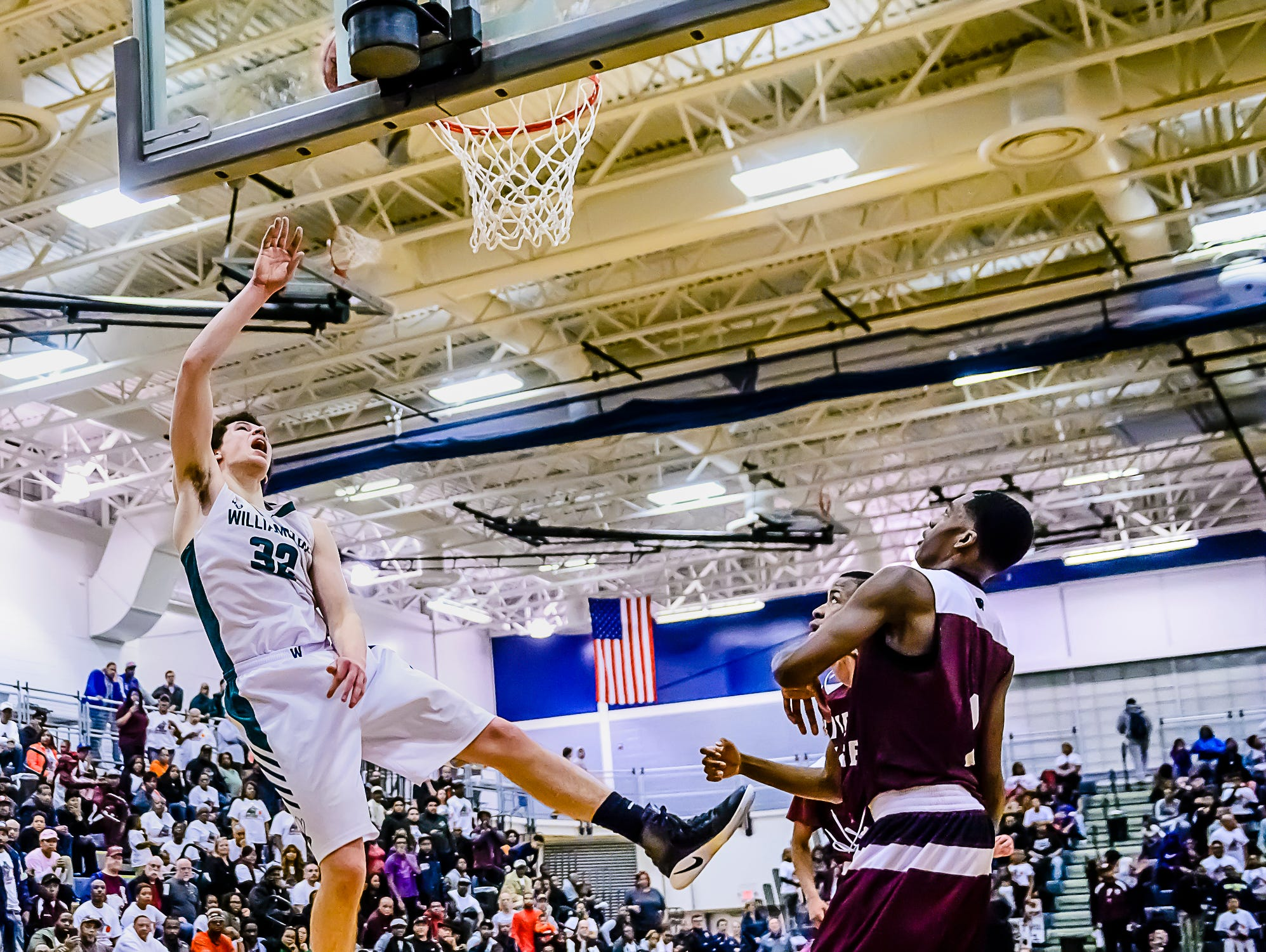 Sean Cobb ,left, of Williamston lays the ball in over River Rouge defenders to put Williamston up 50-49 with 1:15 remaining in their Class B state quarterfinal game Tuesday March 21, 2017 at Chelsea High School in Chelsea. KEVIN W. FOWLER PHOTO