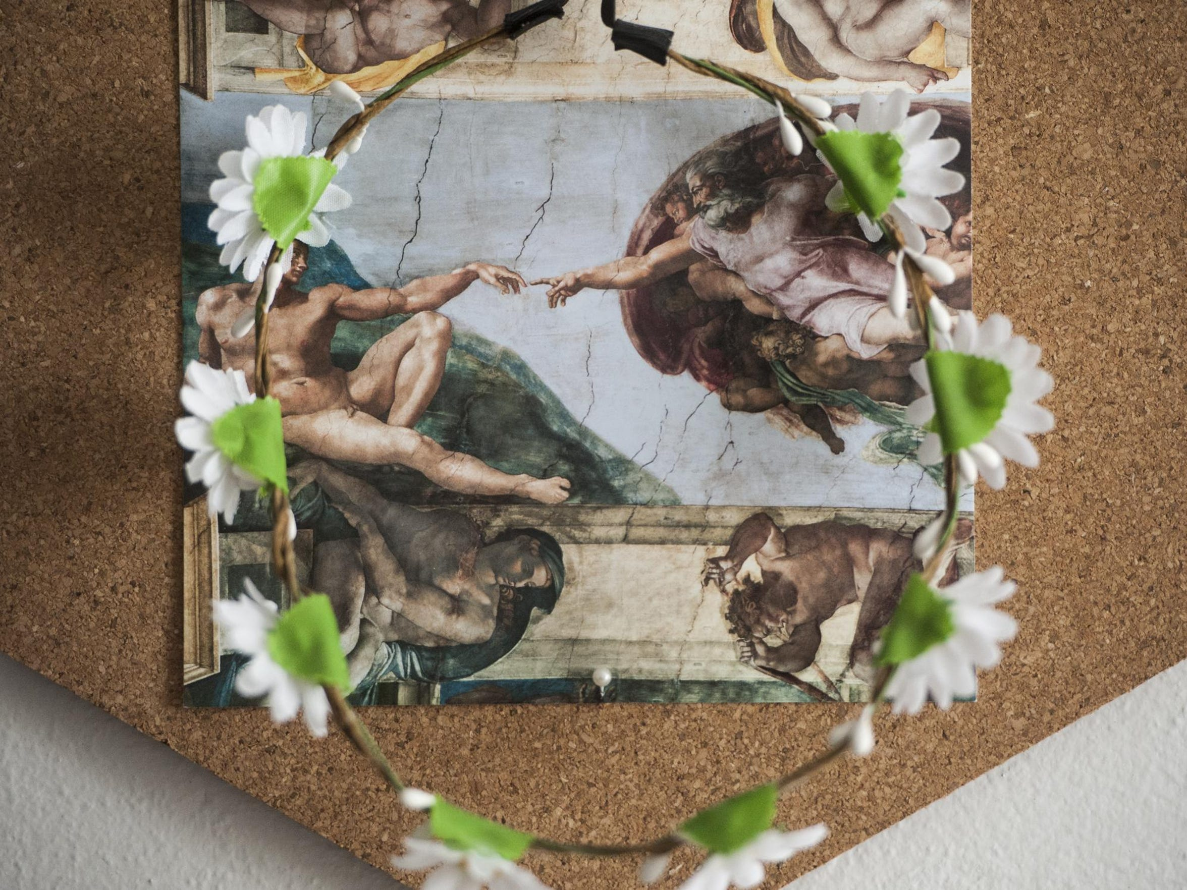 "A flower crown hangs before a print of Michelangelo's ""Creation of Adam"" in Lauren Rhoda's room."