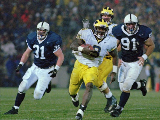 Michigan running back Chris Howard (8) eludes Penn State tacklers  Mac Morrison (31) and Chris Snyder (91) as he races for a 29 yard touchdown in the third quarter of game at State College, Pa. Saturday, Nov. 8, 1997. The Wolverines overwhelmed the  Nittany Lions 34-8.