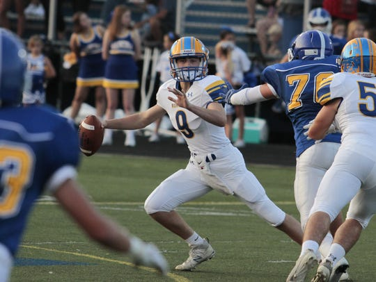 Mariemont quarterback Wally Renie is forced to scramble