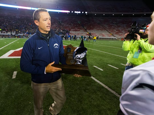 Lake Country Lutheran head coach Greg Brazgel carries the runner-up trophy back to his squad after the Lightning lost to Amherst in the WIAA Division 5 state football championship game on Thursday at Camp Randall Stadium.