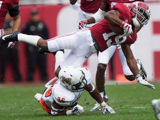Alabama wide receiver Xavian Marks (19) is upended