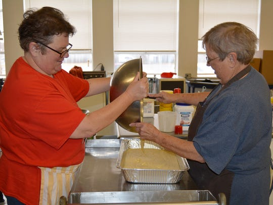 Sharon Goins (left) and Patsy McCarty pour cornbread