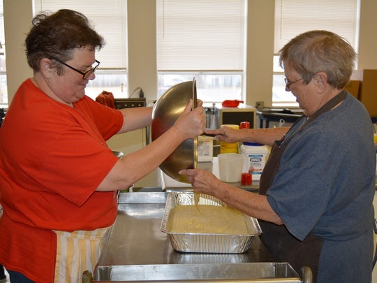 Sharon Goins (left) and Patsy McCarty pour cornbread batter into one of several pans to be baked and used to make dressing for the 31st annual Christmas Day Holiday Meal.