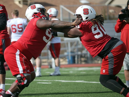 """Eurndraus Bryant, 91, left, and Ben """"Shug"""" Frazier, 90, both defensive tackles, run drills at the start of North Carolina State's football practice Tuesday at Pebble Hills High School."""