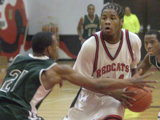 Dwight Buycks prepares to pass to an open teammate after splitting Milwaukee Madison defenders Cordarrius Paige (21) and James Butler (right) in a 2007 game.