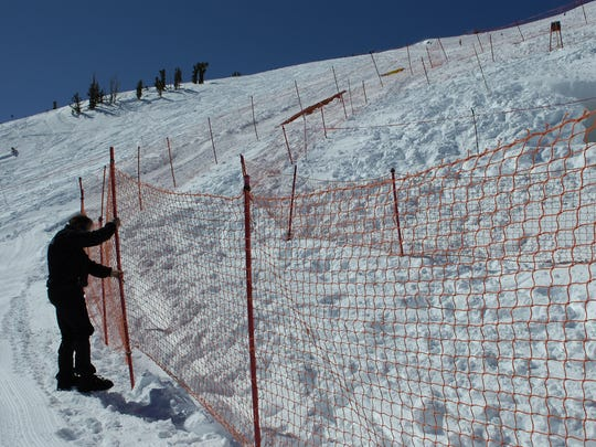 Mammoth Mountain Senior VP Bill Cockroft fixes the safety fence around a volcanic feature where three experienced ski patrollers died in an accident when the deep snowpack around a well-known dangerous volcanic feature collapsed and they fell 21 feet into a gas-filled cavern as they were trying to place the safety fence around the feature after a heavy snowfall Wednesday morning.
