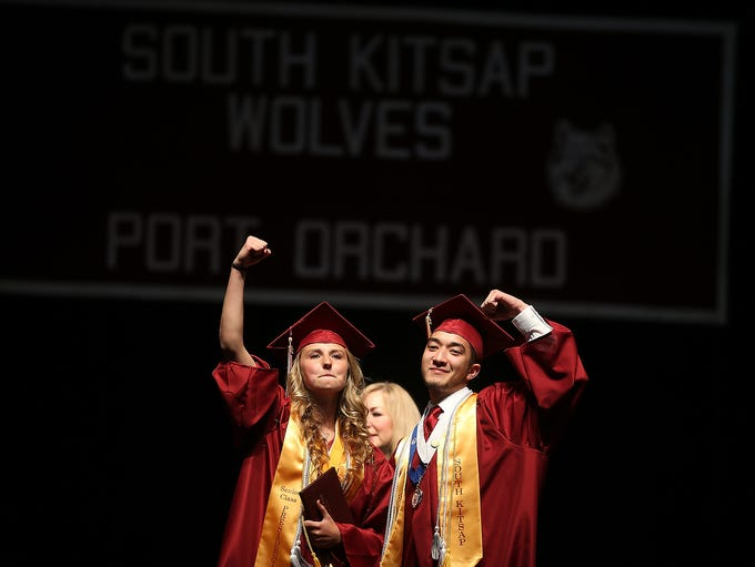 The first two grads to receive their diplomas raise