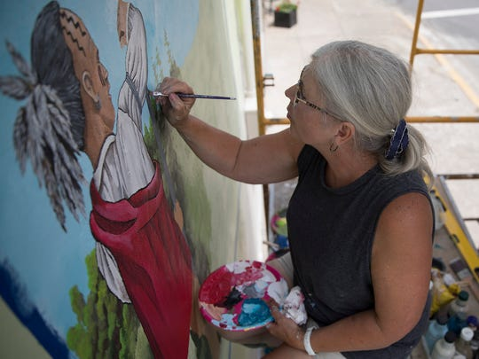 Mural artist Pam Kellough repaints a mural on the brick building beside the Dairy Cone in Frankfort, Ohio, that will eventually depict the town's annual festival, agriculture, the Ross County Fair, Shawnee Native American, veterans, and local landmarks.