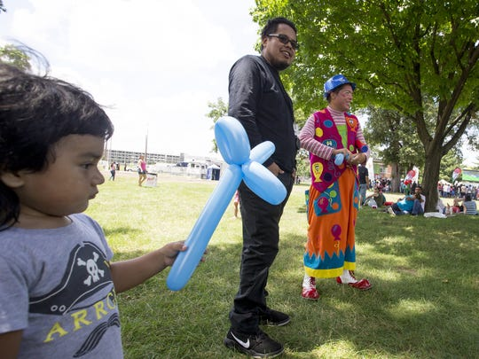 Christopher Hidalgo, left, and Mario Hidalgo, middle, purchase a balloon from Elel Barrg during the Familia Fest at Military Park in Indianapolis on Sunday, June 24, 2018.
