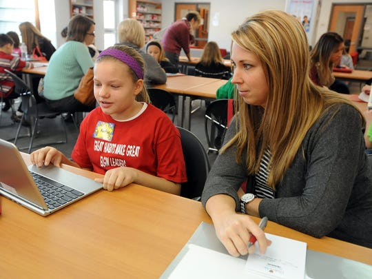 Elgin fifth-grader Katie Yates, left, shows Angie Sprang, vice president of the Fostoria City Schools' Parents Teacher Organization, her leadership plan on her laptop during the elementary school's Leadership Day on Thursday. Leadership Day is held by elementary schools going through the Leader In Me process.