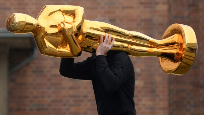 A worker carries an Oscar statue to a press event in Germany in February 2015.